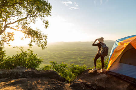 Silhouette of woman travel relax camping in autumn holiday. On top of moutain. Enjoy sunrise, The concept life of freedom.