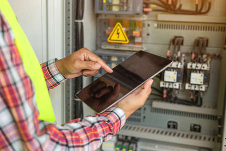 Close up hand of engineer or electrician man working check the electrical system with tablet at factory. Фото со стока