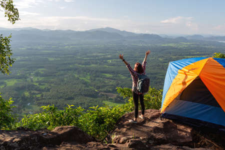 Woman travel relax camping in autumn holiday. On top of moutain. Enjoy sunrise with hands up, The concept life of freedom.