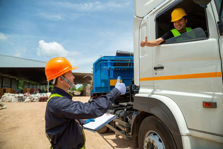 Asian foreman with safety hats and safety vest is carrying a car inspection document in the parking with truck drivers,Concept of planning work day. Road transport safety concept