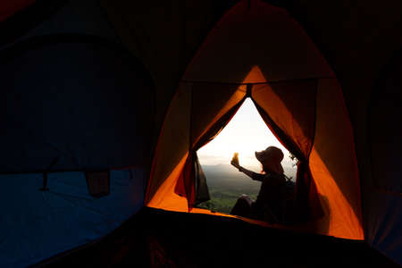 The silhouette of a woman taking selfie in mountains from her.  Camping Travel, lifestyle Фото со стока
