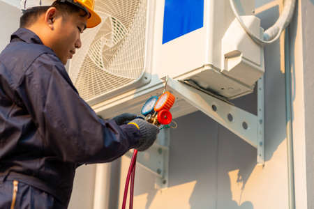 Asian technician is checking air conditioner, After-sales service concept