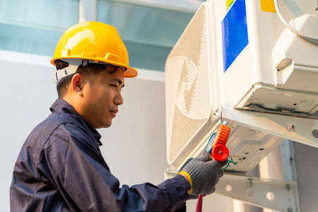 Technician vacuum pump evacuates and checking air conditioner, After-sales service concept Фото со стока