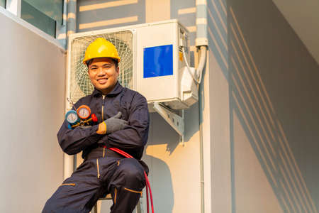 Happy asian technician is checking air conditioner, After-sales service concept