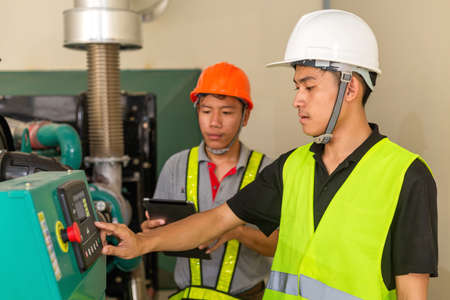 Two asian maintenance technician checking technical data of water pressure control system equipment in factory