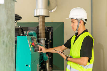 Asian maintenance technician checking technical data of water pressure control system equipment in factory.