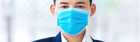 Business man wearing protection face mask against coronavirus. Banner panorama people preventive coronavirus disease or COVID-19 gear.