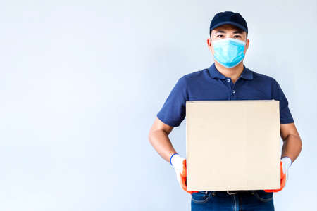 Asian delivery man employee in blue cap blank t-shirt uniform face mask gloves hold empty cardboard box isolated on white background , Concept of prevention of the spread of coronavirus Фото со стока