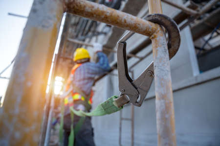 Construction worker wearing safety harness and safety line working at high place, Fall arrestor device for worker with hooks for safety body harness on selective focus. Worker as in construction site. 版權商用圖片