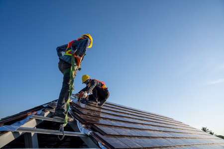 Construction worker wearing safety height equipment harness belt during working install new ceramic tile roof of building with Roofing tools electric drill used in the construction site.