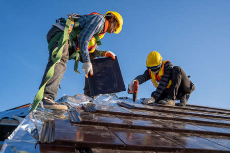 Two work construction worker install new ceramic tile roof with Roofing tools electric drill used in the construction site.