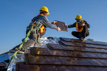 Team work construction worker install new ceramic tile roof with Roofing tools electric drill used in the construction site.