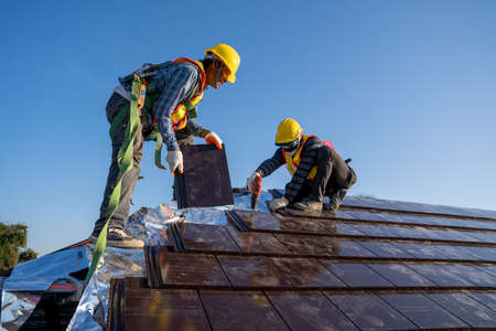 Two work construction worker wearing safety height equipment harness belt during working and install new ceramic tile roof with Roofing tools electric drill used in the construction site. Zdjęcie Seryjne