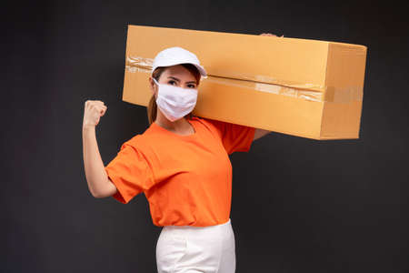Delivery asian woman or courier wearing an orange masked uniform holds a cardboard box and act strong in the coronavirus concept studio. 版權商用圖片