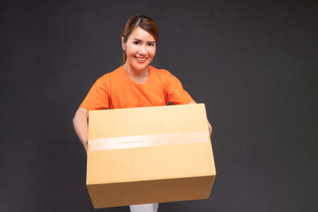 Delivery asian woman or courier wearing an orange uniform holds a cardboard box in studio.