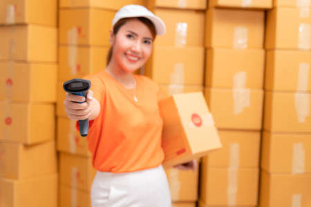 Asian parcel delivery worker in warehouse with barcode scanner.