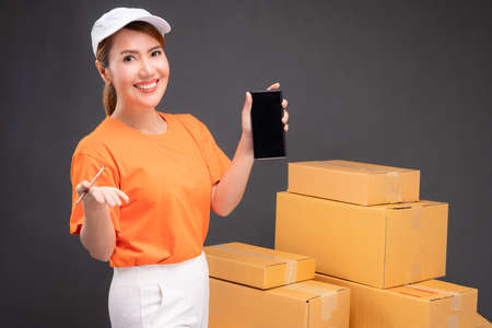 Online shopping with a smartphone start small business in a cardboard box at work. Asian female seller prepares the delivery box for the customer, online sales, or ecommerce. 版權商用圖片
