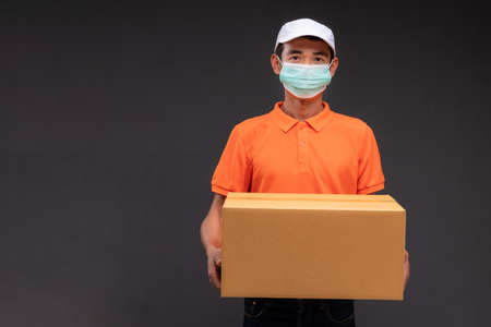 Delivery asian man or courier wearing an orange masked uniform holds a cardboard box in the coronavirus concept studio. 版權商用圖片