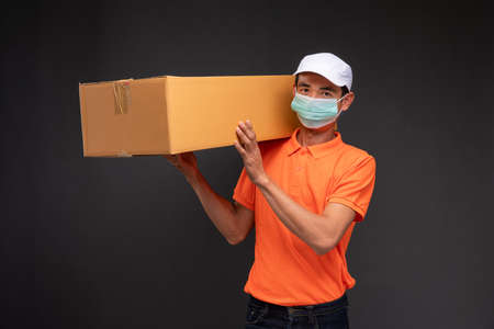 Delivery asian man or courier wearing an orange masked uniform holds a cardboard box