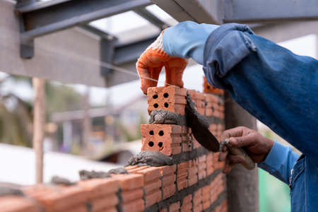Bricklayer worker installing brick masonry exterior wall with trowel putty knife on construction site