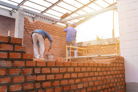 Blurred image of Bricklayer worker installing brick masonry on exterior wall with trowel putty knife on construction site
