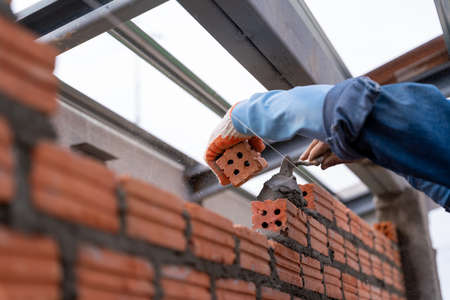 Hand of Bricklayer worker installing brick masonry on exterior wall with trowel putty knife on construction site