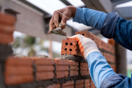 Close up hand of Bricklayer worker installing brick masonry on exterior wall with trowel putty knife on construction site 版權商用圖片