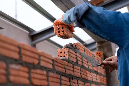 Close up hand of Bricklayer worker installing brick masonry on exterior wall on construction site