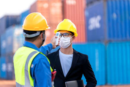 Asian worker scanning fever temperature with digital thermometer to industry construction site staff wearing hygiene face mask protect from Coronavirus or COVID-19. New Normal 版權商用圖片