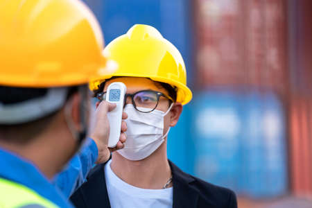 Close up asian worker scanning fever temperature with digital thermometer to industry construction site staff wearing hygiene face mask protect from Coronavirus or COVID-19. New Normal