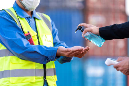 Worker wash your hands with gel and scanning fever temperature with digital thermometer to industry construction site staff wearing hygiene face mask protect from Coronavirus or COVID-19. New Normal 版權商用圖片