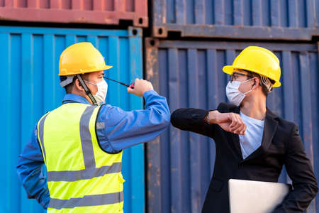 Asian industry construction site worker and foreman wearing hygiene face mask elbow bump greeting adaptation to prevent Coronavirus or Covid-19 spreading at warehouse, New Normal 版權商用圖片