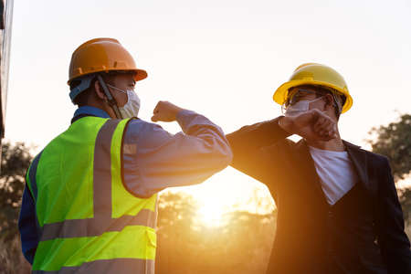 Asian industry construction site worker and foreman wearing hygiene face mask elbow bump greeting adaptation to prevent Coronavirus or Covid-19 spreading at warehouse near the sunset, New Normal