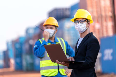 Asian male logistic warehouse foreman with worker using laptop checking list planning and strategy of container boxes from cargo freight ship. industry import export shipping business. 版權商用圖片