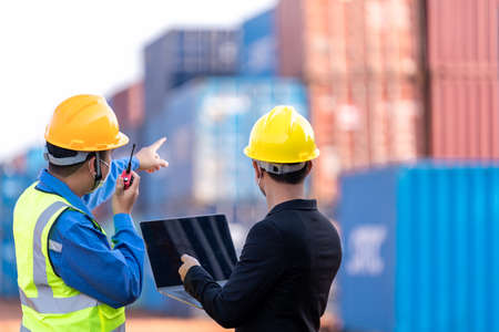 Teamwork, Asian male logistic warehouse foreman with worker using laptop checking list planning and strategy of container boxes from cargo freight ship. industry import export shipping business.