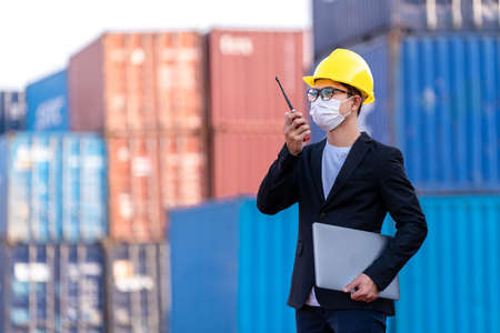 Asian male wear a mask use a radio to command logistic warehouse foreman checking list container boxes. industry import export shipping business, During the spread