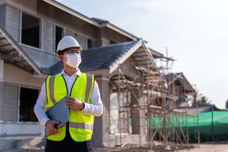 Portrait of Architect wearing a mask hold a laptop on a building construction site, Homebuilding Ideas and Prevention