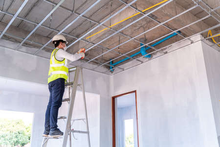 Asian electrician wearing a mask installing laying electrical cables on the ceiling with pliers inside the house under construction.