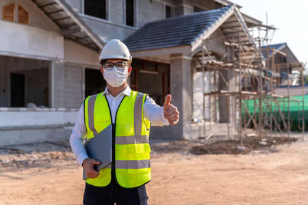 Portrait of Architect wearing a mask on a building construction site, Homebuilding Ideas and Prevention of  Disease. 版權商用圖片