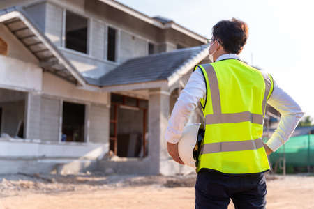 Architect watching some details and hold a helmet on a construction, House builder concept. 版權商用圖片