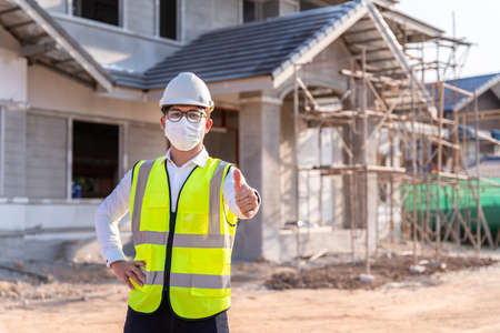 Portrait of Architect wearing a mask reassure on a building construction site, Homebuilding Ideas and Prevention 版權商用圖片