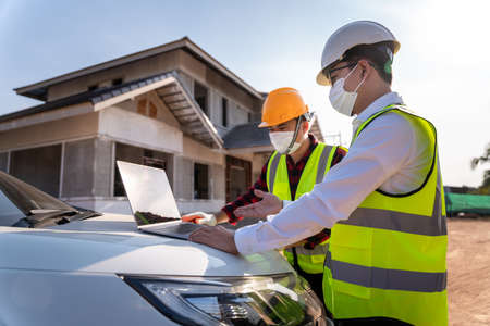 Architect and Supervisors using laptop at construction site, House construction