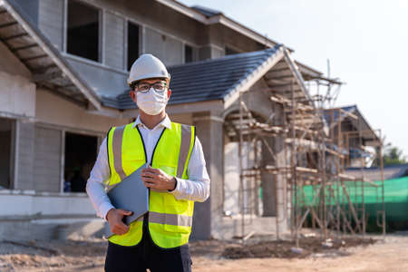 Architect wearing a mask hold a laptop on a building construction site, Homebuilding Ideas and Prevention of  Disease. 版權商用圖片