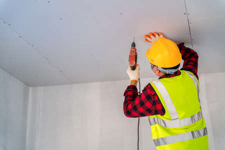 Construction worker used electric drill installation ceiling.