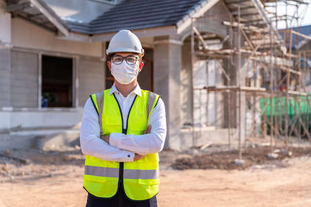 Portrait of Architect wearing a mask on a building construction site, Homebuilding Ideas and Prevention 版權商用圖片
