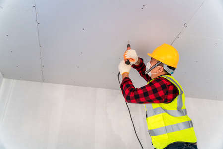 Construction worker wearing a mask used electric drill installation ceiling.