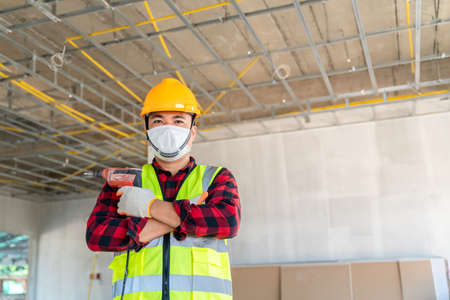 Portrait of Construction worker wearing a mask hold electric drill installation ceiling. 版權商用圖片