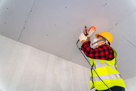 Asian construction worker used electric drill installation ceiling.