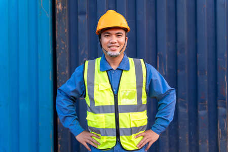 Portrait of Asian workers import and export goods wear a helmet logitics shipping at container background.