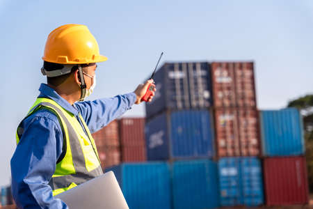 foreman worker wear a mask working use a long distance radio control container cargo harbor to loading containers. Logistics import export shipping concept. 版權商用圖片